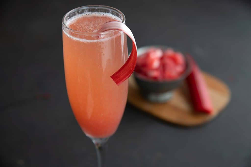Close up shot of the top of a champagne flute filled with rhubarb fizz cocktail.