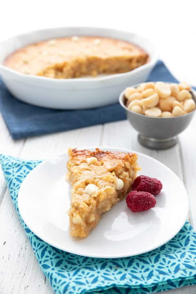 A slice of macadamia nut pie on a white plate with the whole pie in the background.
