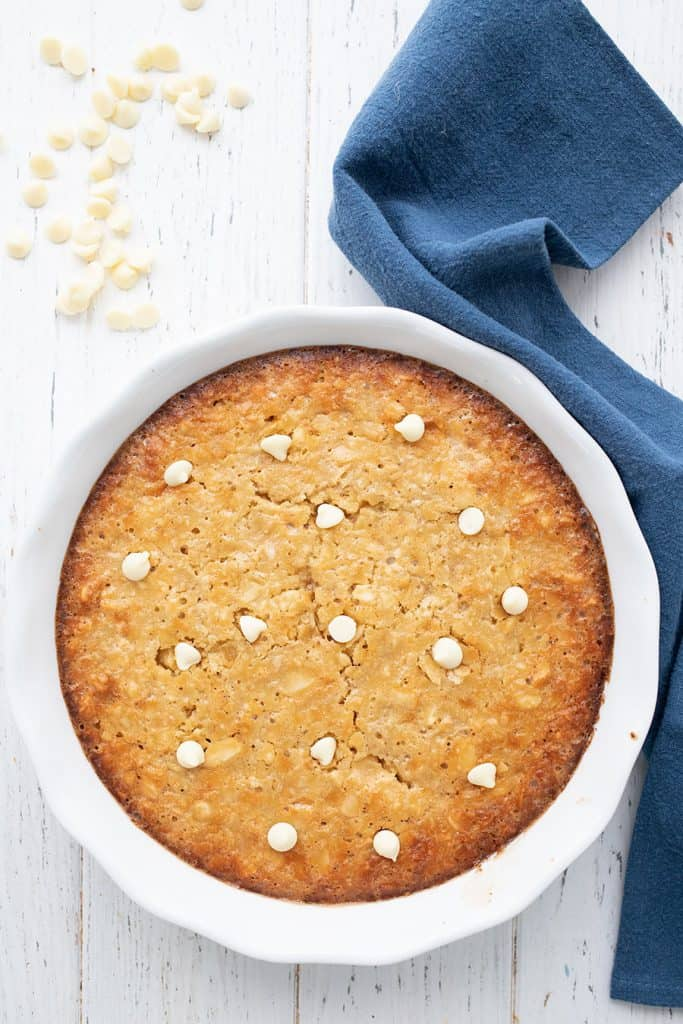Top down image of keto macadamia nut pie on a white table, with a scattering of white chocolate chips.