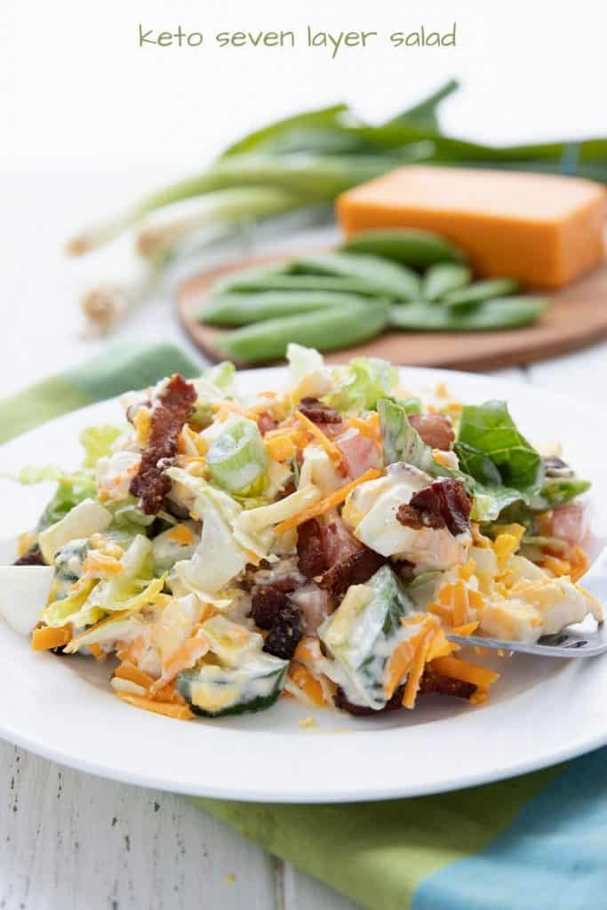Titled image of a white plate filled with Keto Seven Layer Salad