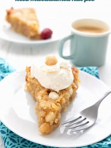 Titled image: a slice of keto macadamia nut pie on a white plate over a blue patterned napkin, with a scoop of ice cream on top.