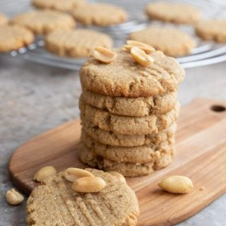 Titled image of a stack of keto peanut butter cookies on a wooden cutting board with peanuts sprinkled around.