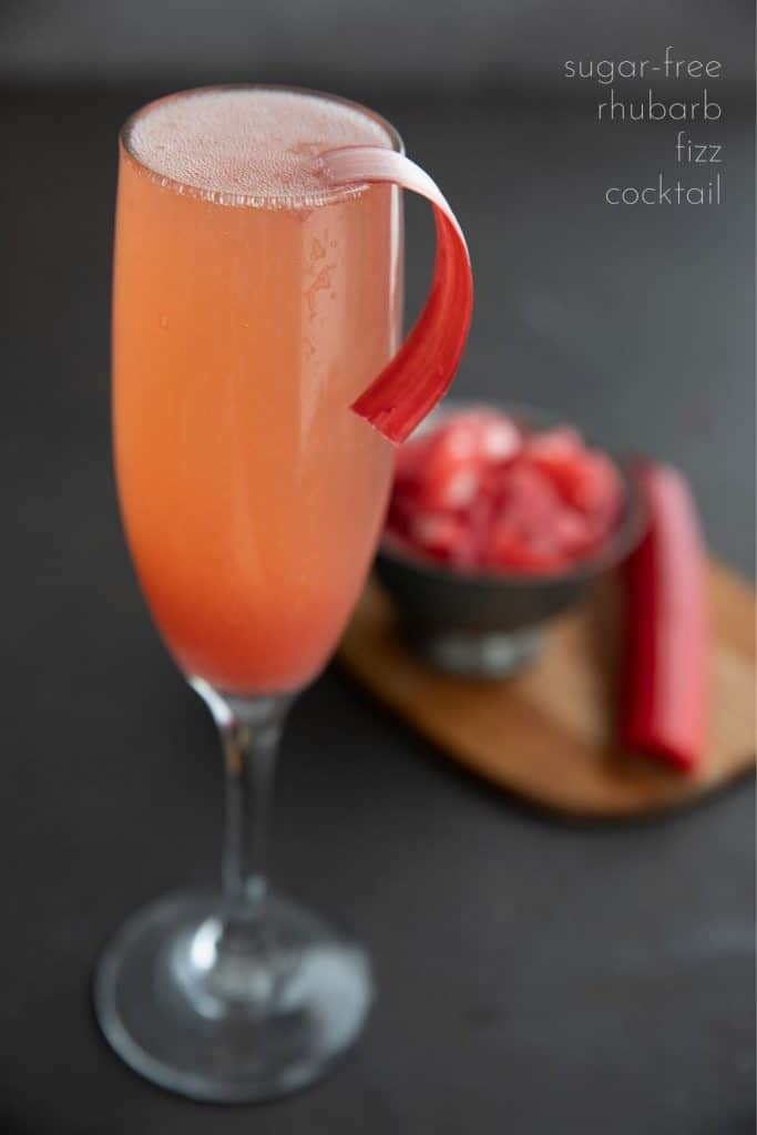 Titled image of a sugar free rhubarb cocktail in a champagne flute with a strip of peeled rhubarb as garnish.