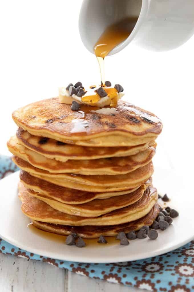 Sugar free syrup being poured over a stack of keto pancakes