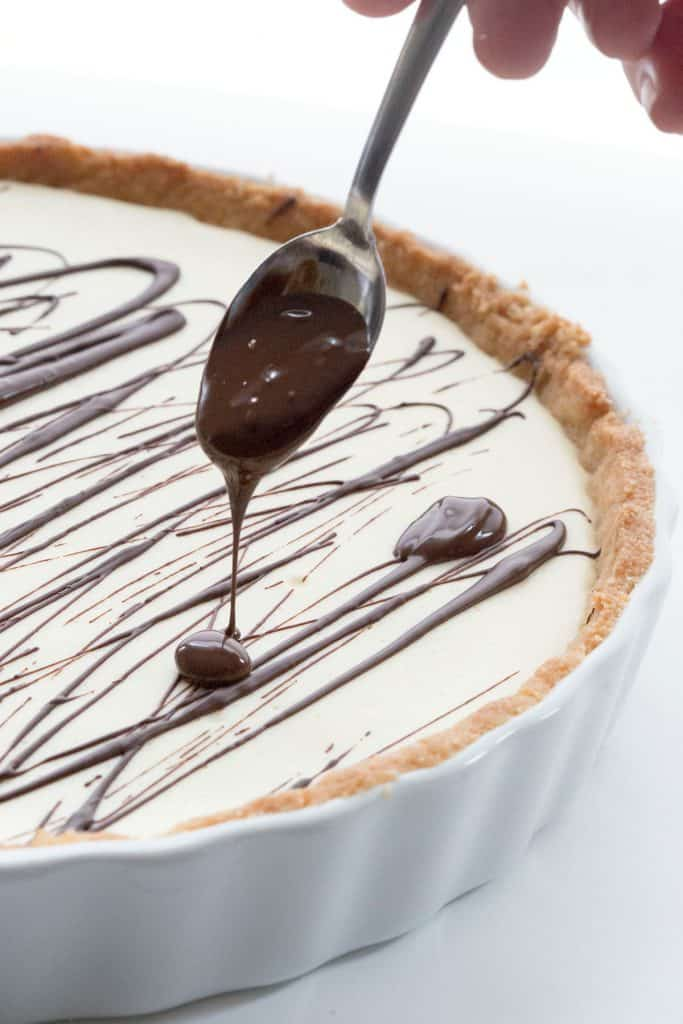 A spoon drizzling chocolate over a pan of keto cannoli tart.