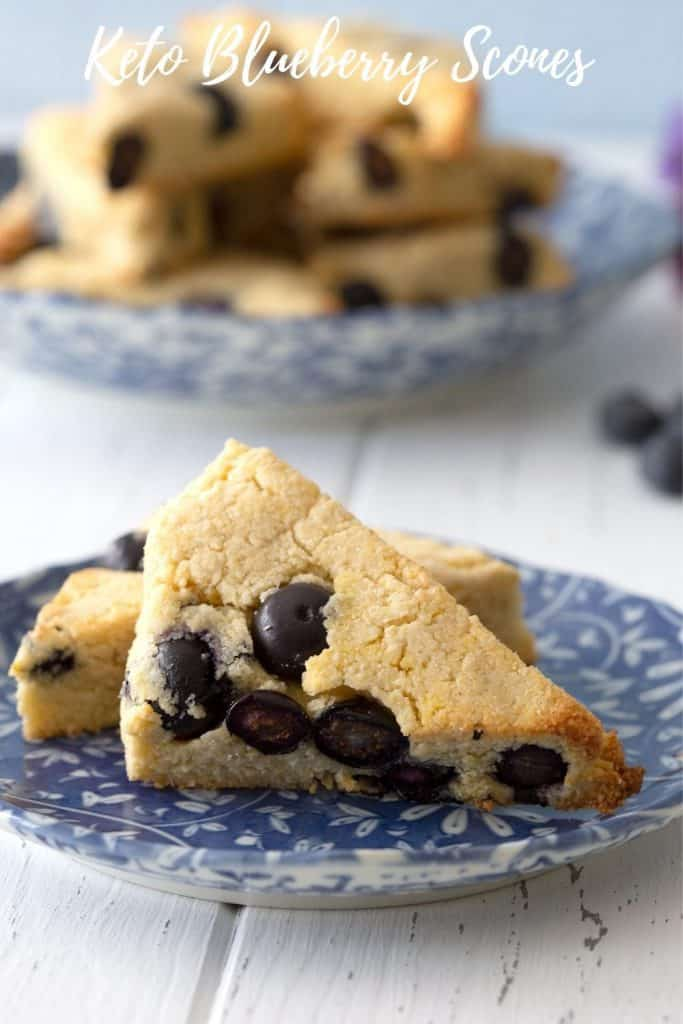 Titled image of two keto blueberry scones an a blue patterned plate, with a larger plate of scones in the background.