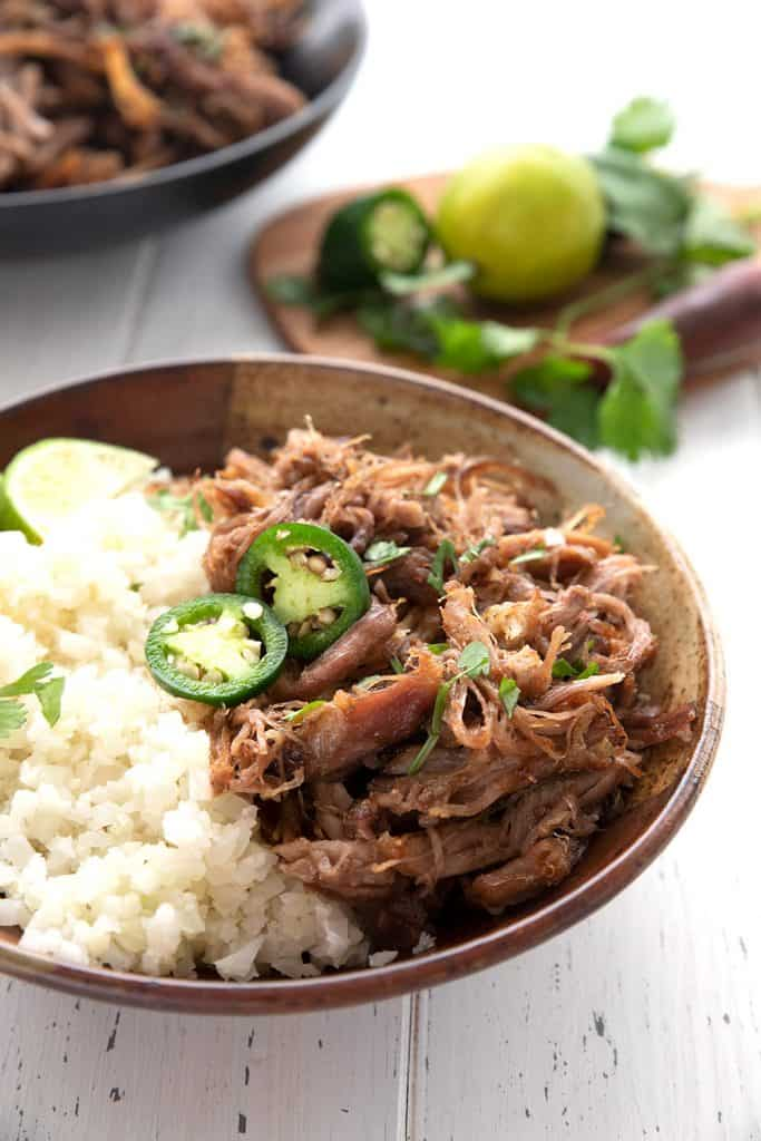A bowl of keto carnitas sits in front of a cutting board with lime, cilantro, and jalapeno.