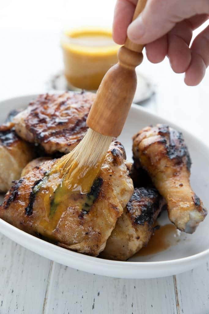 Sugar free Carolina style bbq sauce being brushed over a plate of grilled chicken.