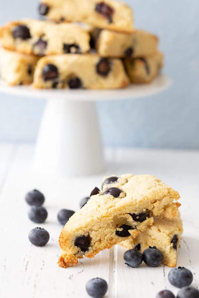 Two keto blueberry scones sit on a white table with blueberries scattered around.
