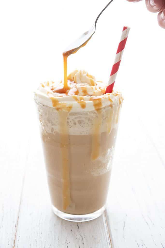 A spoon drizzling sugar free caramel sauce over a keto frappuccino