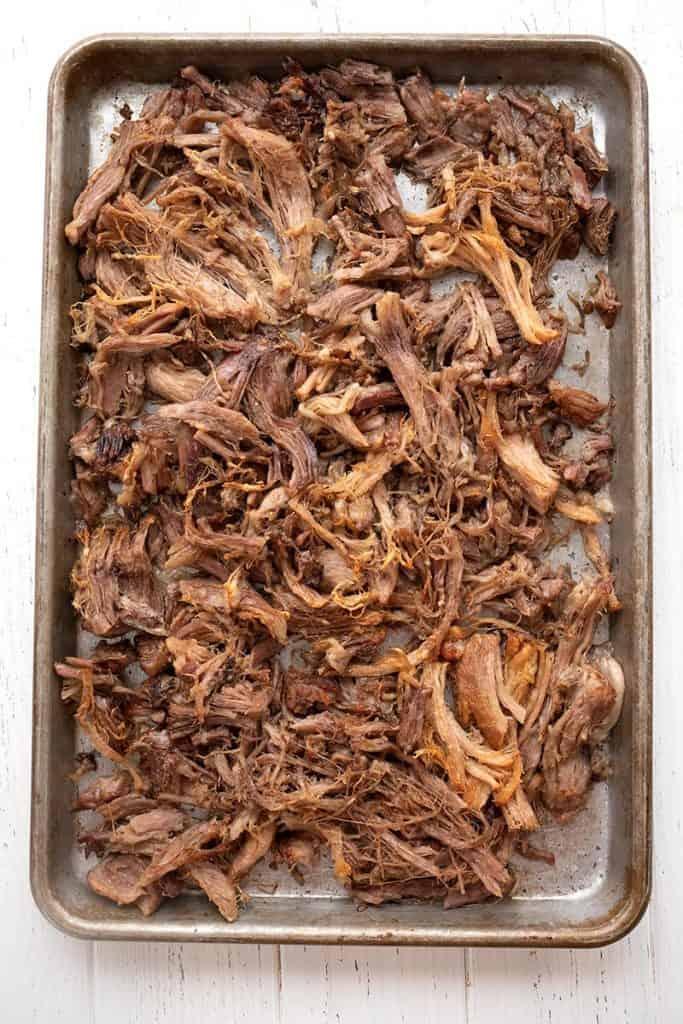 Top down image of a metal baking pan filled with roasted pork carnitas.