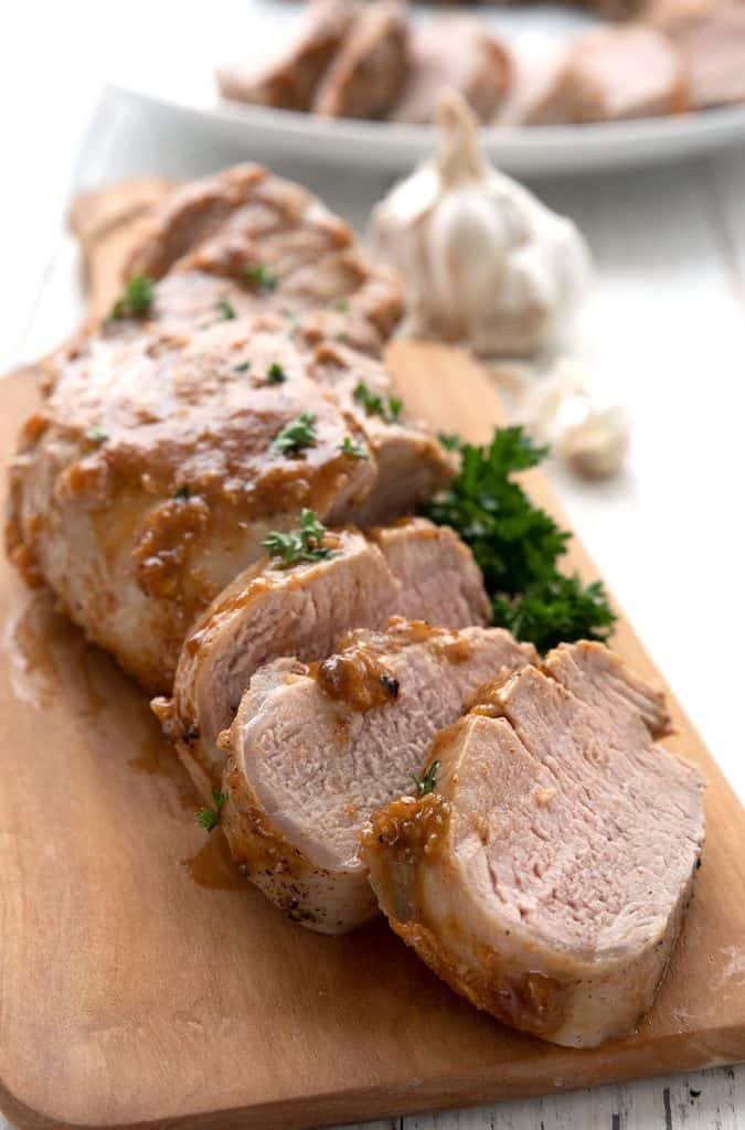 Slices of keto pork tenderloin on a cutting board with parsley and garlic.