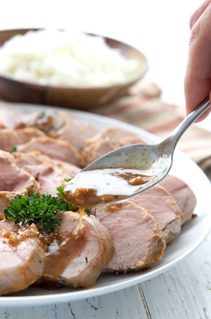 A spoon drizzling garlic sauce over pork tenderloin.