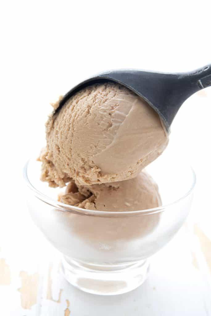An ice cream scoop putting keto caramel ice cream into a bowl.