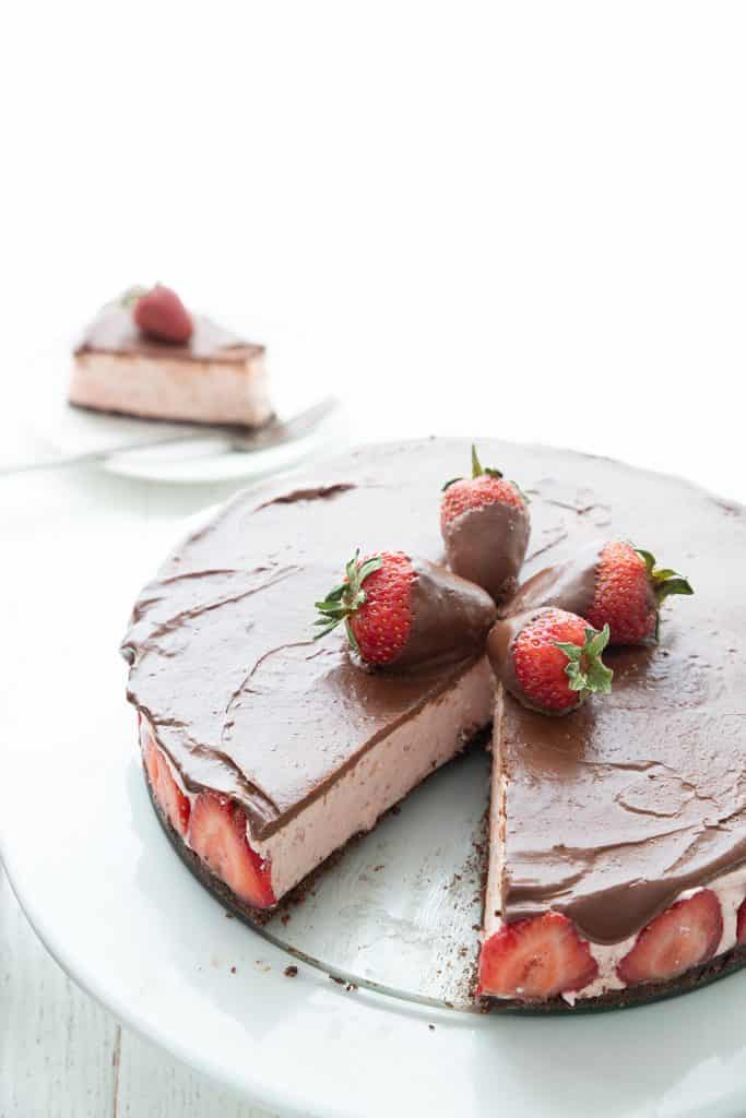 No Bake Strawberry Cheesecake on a white cake plate with a slice taken out of it.