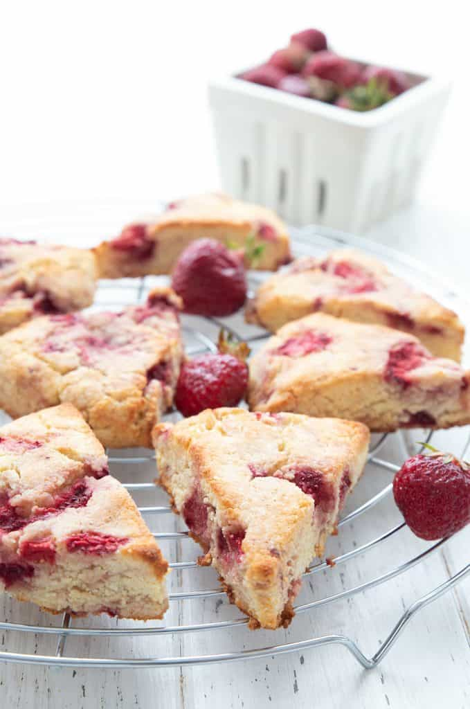 Strawberry scones on a cooling rack in front of a basket of strawberries.