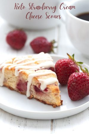Titled image of a keto strawberry scone on a white plate, with fresh strawberries