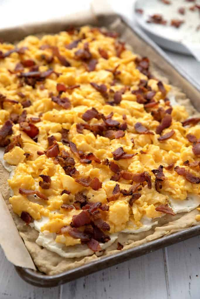 Sheet pan breakfast pizza topped with bacon and eggs.