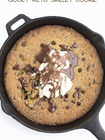 Top down image of a keto skillet cookie topped with ice cream and chocolate sauce.
