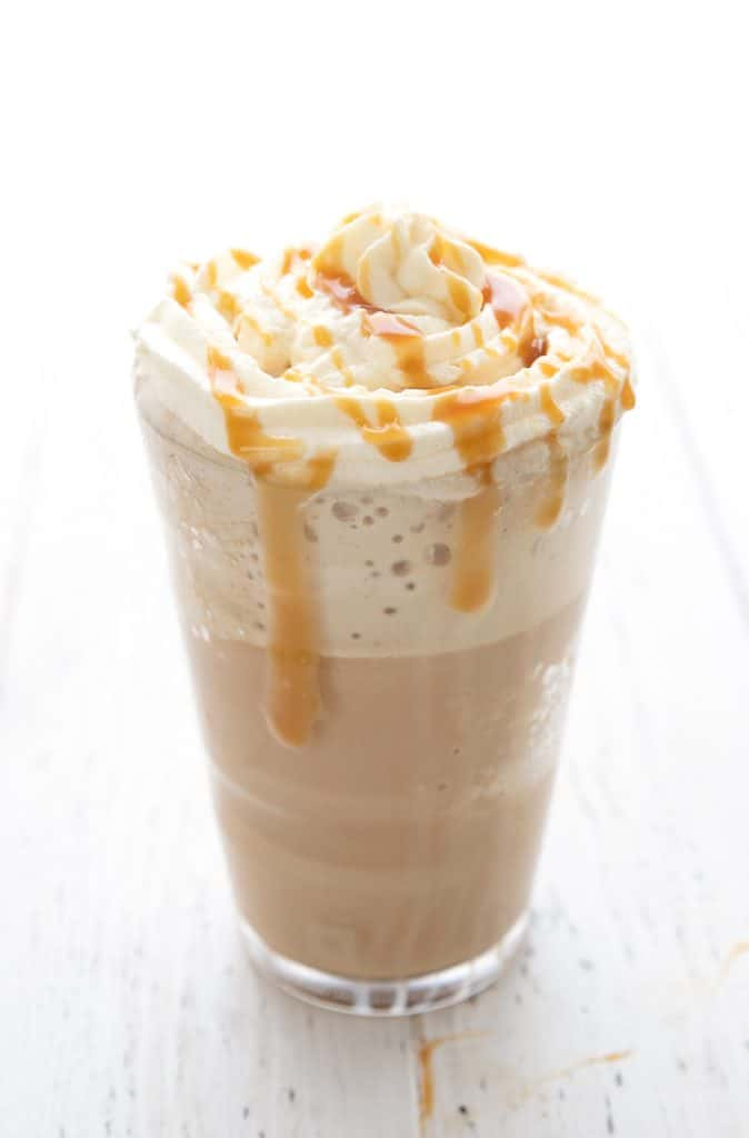 A single sugar free caramel frappuccino on a white table with caramel sauce on top.