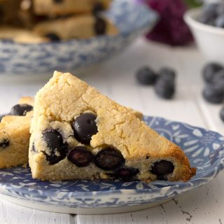 Close up shot of two blueberry scones on a blue patterned plate.