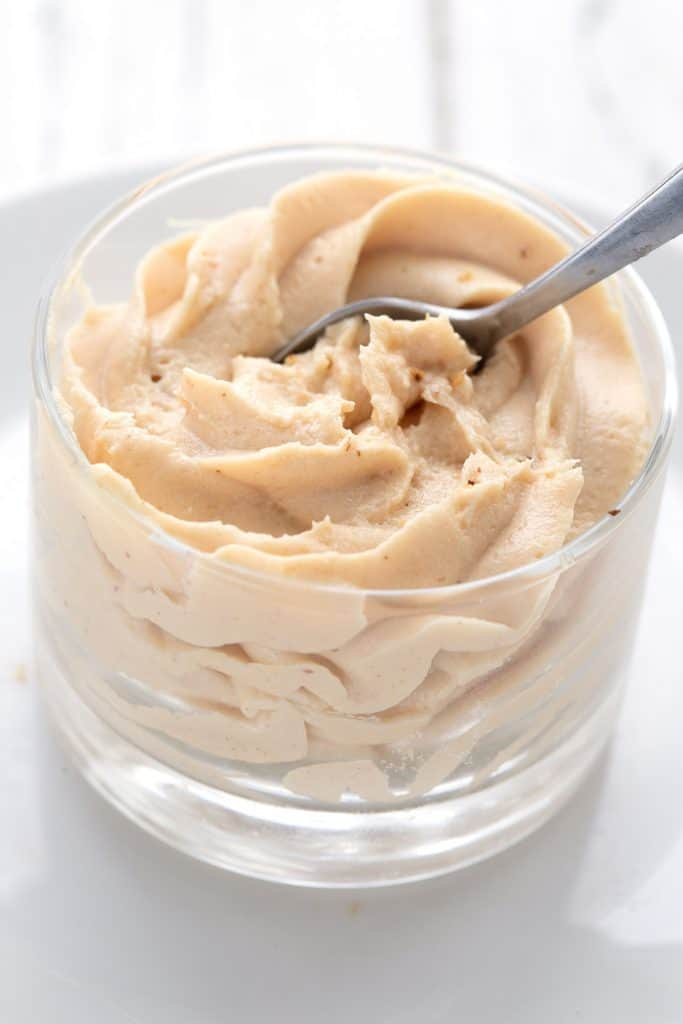 A spoon digging into a dessert cup filled with peanut butter mousse.
