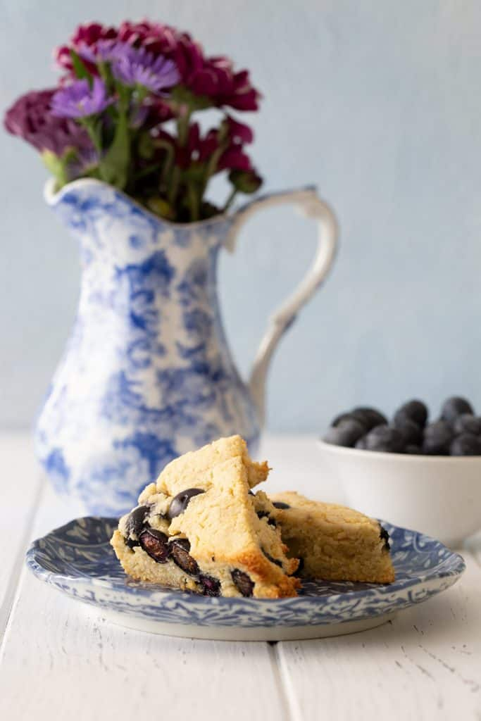 Keto Blueberry Scones on a blue plate in front of a bowl of berries and a blue patterned pitcher filled with purple flowers.