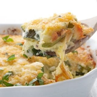A wooden spoon lifting zucchini casserole out of a white casserole dish.