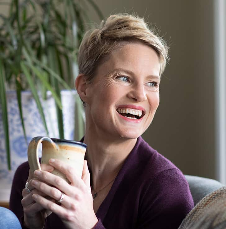 Photo of Carolyn Ketchum drinking coffee and laughing.