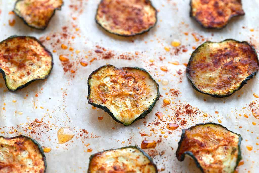 Zucchini chips on a parchment lined baking sheet.