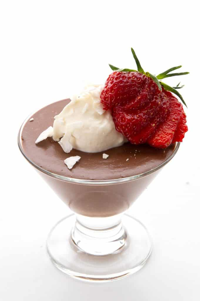 Keto chocolate pudding in a glass dessert cup with whipped cream and a strawberry on top.