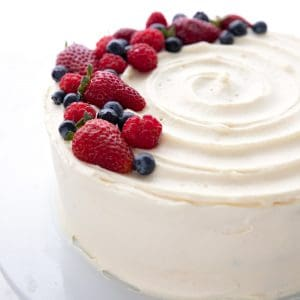 Keto Chantilly Cake on a white cake plate with berries on top.