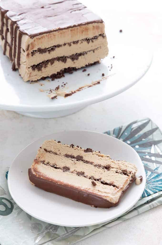 Easy coffee ice cream cake on a white cake platter, with a slice on a white plate in front.
