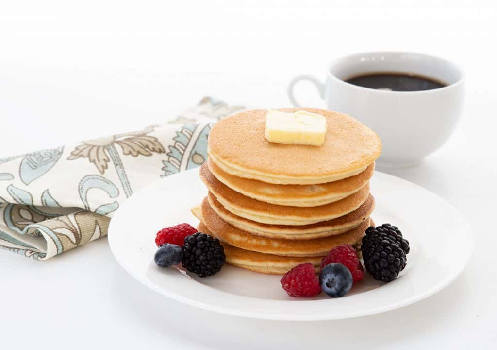 A stack of keto pancakes on a white plate with a pat of butter on top. A cup of coffee and a napkin in the background.