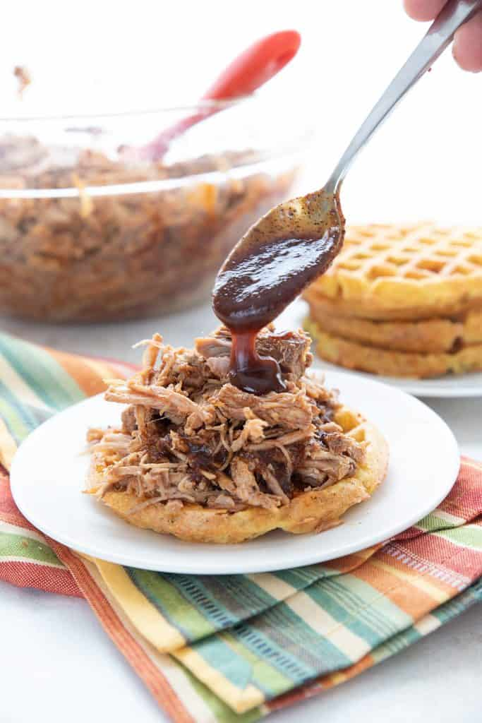 A spoon drizzling sugar free bbq sauce over keto pulled pork on a white plate.