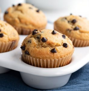 Close up shot of keto chocolate chip muffins a white muffin pan.