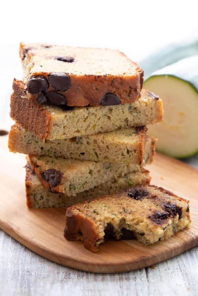 A stack of slices of chocolate chip keto zucchini bread on a wooden cutting board.