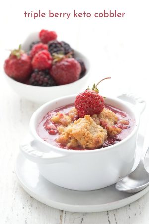 Titled image of triple berry keto cobbler in a white ramekin, with a bowl of berries in the background.