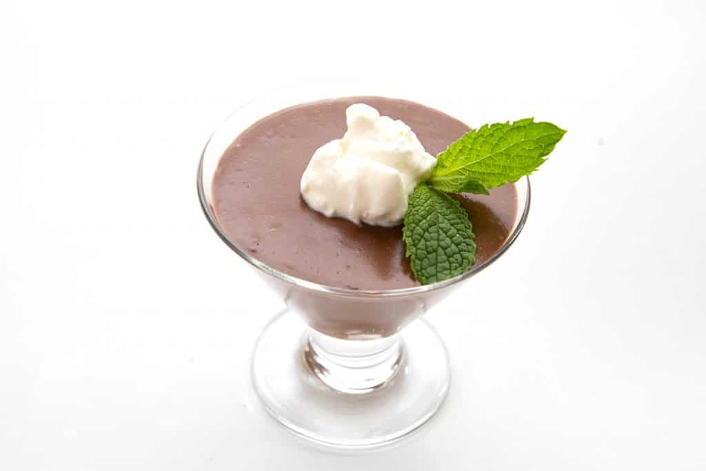 Close up shot of keto chocolate pudding with whipped cream and a mint leaf on top.