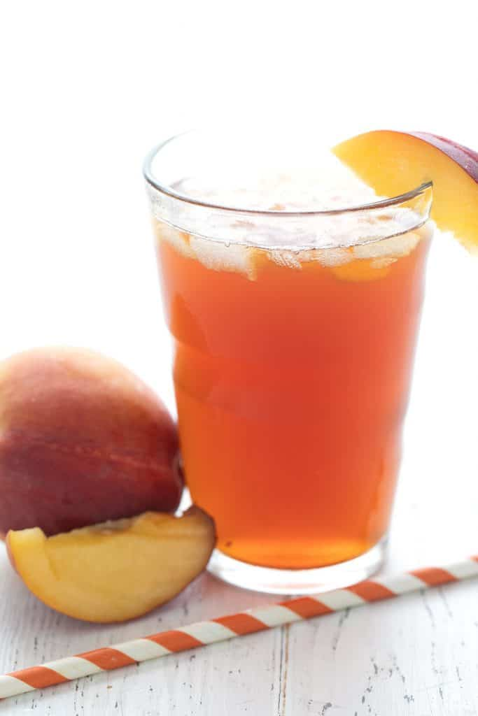 A glass full of keto sweet tea with peaches and a striped orange straw, on a white wooden table.