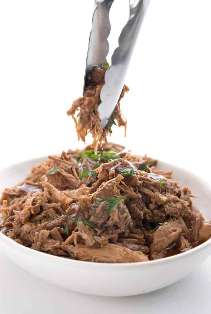 Tongs lifting some keto instant pot pulled pork above an oval dish.