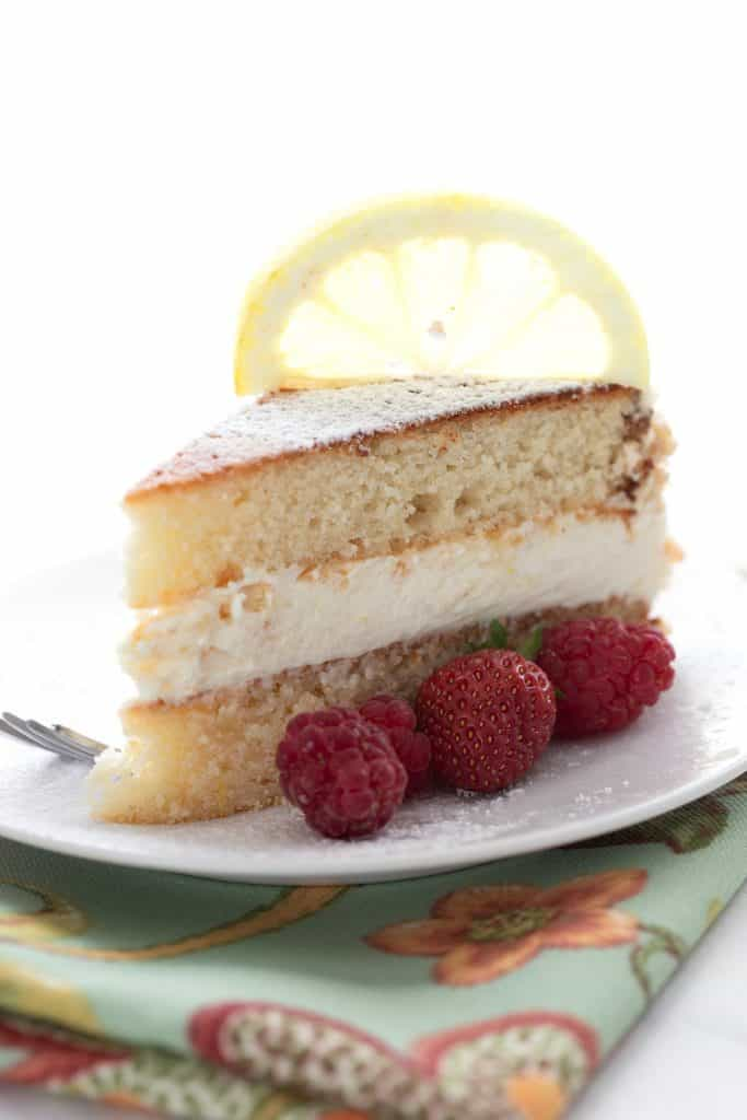 A slice of keto lemon cake on a white plate with berries on the side and a lemon slice on top.