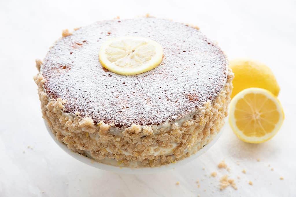 A keto lemon cake on a white cake stand beside some cut lemons.