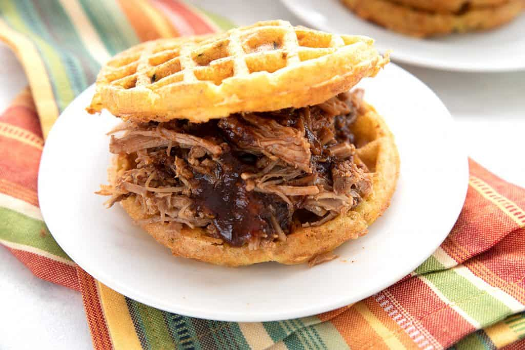 A keto pulled pork sandwich on low carb waffles, on a white plate over a colourful striped napkin.