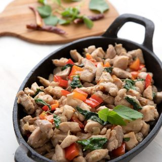 Titled image of Keto Thai Basil Chicken in a cast iron pan.