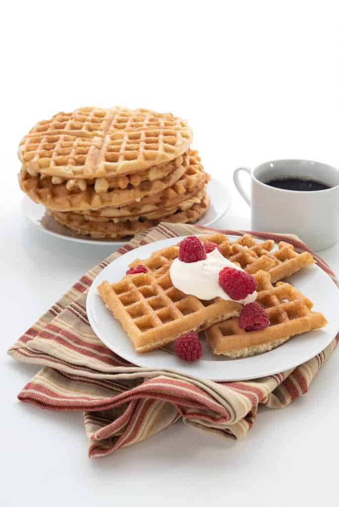 Keto waffles on a white plate over a striped tan and red napkin. A stack of waffles and a cup of coffee in the background.