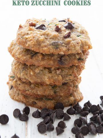 Titled image of keto zucchini cookies in a stack with chocolate chips around the base.
