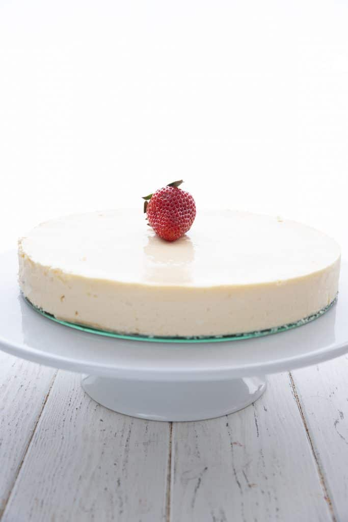 Crustless keto cheesecake on white cake stand, with a single strawberry on top.