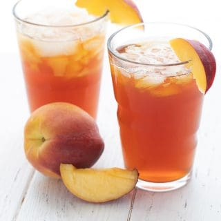 Two glasses of sweet peach tea on a white table with sliced peaches.