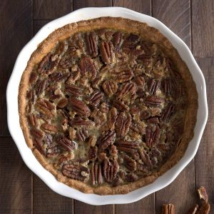 Top down image of keto pecan pie in a white ceramic pie plate on a brown wooden table.
